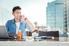 Handsome male person working as freelancer. I am here. Young man sitting at the table and looking sideways while touching his cheek Stock Photography