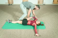 Handsome male personal trainer with a beard helping young fitness girl to stretch her muscles after hard training workout, selecti. Ve focus Royalty Free Stock Photos