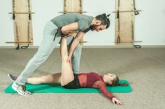 Handsome male personal trainer with a beard helping young fitness girl to stretch her muscles after hard training workout, selecti. Ve focus Stock Image