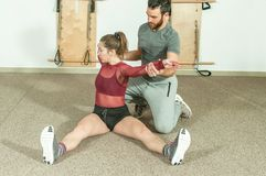 Handsome male personal trainer with a beard helping young fitness girl to stretch her muscles after hard training workout, selecti. Ve focus Stock Images