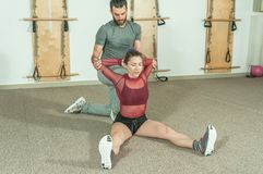 Handsome male personal trainer with a beard helping young fitness girl to stretch her muscles after hard training workout, selecti. Ve focus Royalty Free Stock Photography