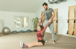 Handsome male personal trainer with a beard helping young fitness girl to stretch her muscles after hard training workout, selecti. Ve focus Royalty Free Stock Images