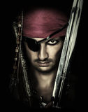 Handsome male pirate holding sword. Portrait of handsome male pirate holding sword on black background Royalty Free Stock Images