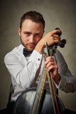 Handsome male playing on antique black cello Stock Photos