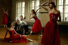 Handsome male playing on cello and four ballerina in red dress dancing around him Royalty Free Stock Image