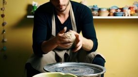 Handsome male potter knead clay before work in the pottery workshop. Art concept stock video footage