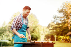 Handsome male prepares barbecue. Outdoors Stock Photography