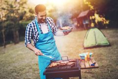 Handsome male preparing barbecue Stock Images