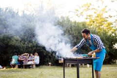Handsome male preparing barbecue Royalty Free Stock Images