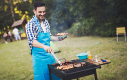 Handsome male preparing barbecue Royalty Free Stock Photography