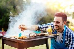 HAndsome male preparing barbecue Stock Photos