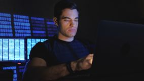 Handsome male programmer working at a computer at night in the office filled with monitor screens. Handsome male programmer geek working at a computer at night stock video footage