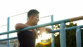 Handsome male relaxing after training on crossbars at sunset, sport hobby. Stock photo stock photos