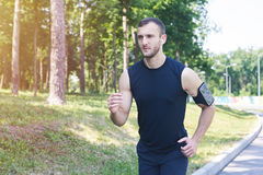 Handsome male running in park while listening to music. Wide shot of handsome male running in park while listening to music Royalty Free Stock Photo