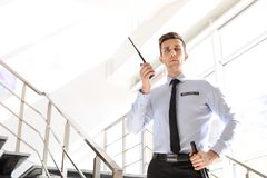 Handsome male security guard with portable radio transmitter indoors. Male security guard with portable radio transmitter indoors Stock Photography