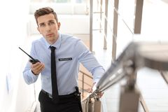 Handsome male security guard with portable radio transmitter indoors. Male security guard with portable radio transmitter indoors Royalty Free Stock Images