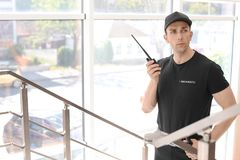 Handsome male security guard with portable radio transmitter indoors. Male security guard with portable radio transmitter indoors Stock Photos