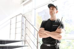 Handsome male security guard with portable radio transmitter indoors. Male security guard with portable radio transmitter indoors Stock Images