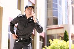 Handsome male security guard using portable radio transmitter outdoors. Male security guard using portable radio transmitter outdoors Royalty Free Stock Images