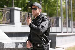 Handsome male security guard using portable radio transmitter outdoors. Male security guard using portable radio transmitter outdoors Royalty Free Stock Photo