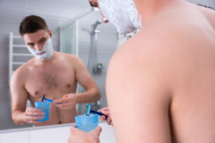 Handsome male with shaving foam on his cheeks washes his razor i. N the cup with water standing in front of mirror in the modern tiled bathroom at home Royalty Free Stock Photography