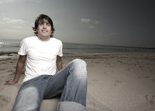 Handsome male sitting on the sand Stock Images