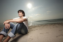 Handsome male sitting on the sand Stock Photography