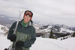 Handsome Male Skier Holding Skis. Portrait of a handsome male skier standing on mountain with skis Stock Image