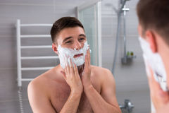 Handsome male smearing foam for shave on his face. Standing in front of mirror in the modern tiled bathroom at home Stock Photo