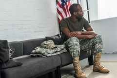 Handsome male soldier sitting on sofa. With camouflage clothes Royalty Free Stock Image