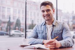 Handsome male student doing task. Self education. Bearded young male student writing down information while smiling and looking at the camera Stock Photography