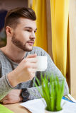 Handsome male student is enjoying hot drink. Attractive young man is drinking a cup of coffee. He is sitting at the table near some papers. The guy is looking Stock Image