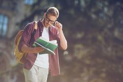Student reading book. Handsome male student in eyeglasses reading book in park Royalty Free Stock Photography