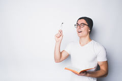 Handsome male student holding notebook. Suddenly interesting idea or plan came up to his mind and he is glad because of that. Eureka Royalty Free Stock Photos
