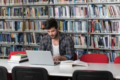Student Learning in Library. Handsome Male Student With Laptop and Books Working in a High School Library Stock Photography