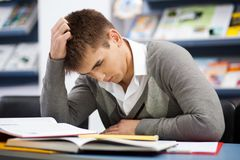 Handsome male student in a library Stock Images