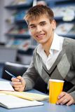 Handsome male student in a library. Handsome male student in a university library Royalty Free Stock Image