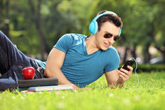 Handsome male student lying on a grass and listening music Royalty Free Stock Photo