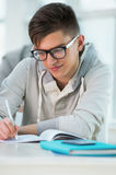 Handsome male student making notes. High School students. Handsome male student making notes in classroom Royalty Free Stock Photography