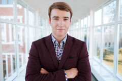 Handsome male student standing with arms folded Royalty Free Stock Photography
