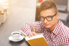 Handsome male student is studying in cafe. Cheerful young man is writing in notebook with seriousness. He is sitting at table in cafe and drinking a cup of Stock Images