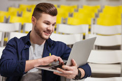 Handsome male student is studying with laptop. Attractive young man is listening to the lecture and smiling. He is typing on a laptop. The man is sitting and Royalty Free Stock Photos