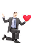Handsome male in a suit kneeling with red heart Stock Photos