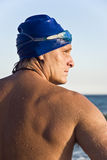 Handsome male swimmer. A colour portrait of a handsome macho looking swimmer wearing a blue cap and goggles and looking to his side Stock Images