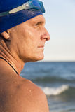 Handsome male swimmer. A colour portrait of a handsome macho looking swimmer wearing a blue cap and goggles and looking to his side.He is standing in profile Royalty Free Stock Photos