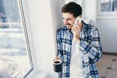 Handsome male talking on cellphone at balcony. A happy young man is using a smart phone in a kitchen and drinking a cup of hot coffee in the morning at home. Top Royalty Free Stock Photography