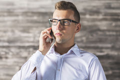 Handsome male talking on phone. Close up portrait of handsome caucasian male talking on phone. Wooden wall background Royalty Free Stock Image