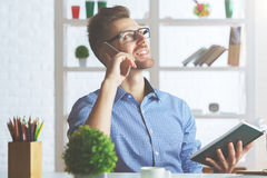 Handsome male talking on phone. Portrait of handsome caucasian male talking on phone at workplace Royalty Free Stock Image