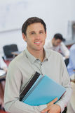 Handsome male teacher posing in his classroom. Smiling at camera Stock Images