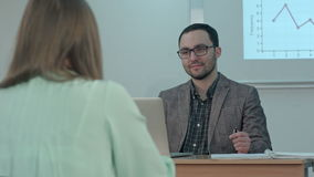 Handsome male teacher smiling and talking with students at the lesson stock video footage